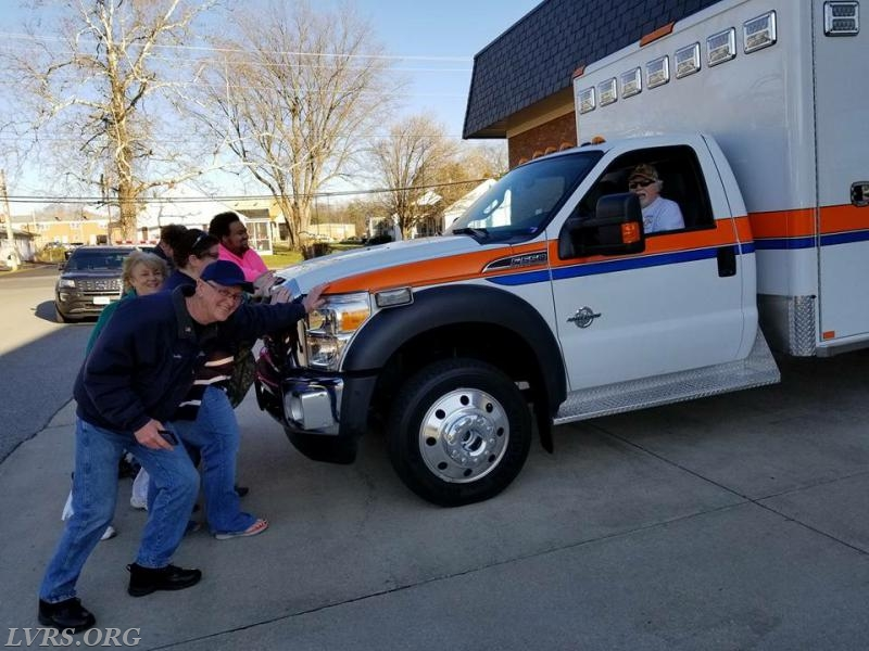 Members helping push the newest ambulance into the squad bay.